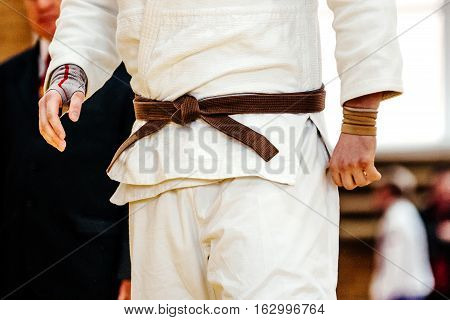 male judo fighter in white kimono with brown belt