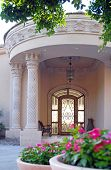image of front door  - welcoming front door entrance with beautiful natural stone and columns with foreground of tree and flowers - JPG