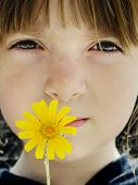 picture of yellow flower  - Young child holding yellow flower to her face - JPG
