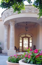 stock photo of front door  - welcoming front door entrance with beautiful natural stone and columns with foreground of tree and flowers - JPG