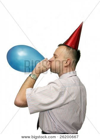 Man wearing party cap inflating blue balloon over white background