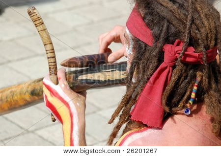 Aborigine-like painted man with dreadlocks playing some primitive wooden instrument