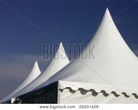 Three white tent tops against deep blue sky