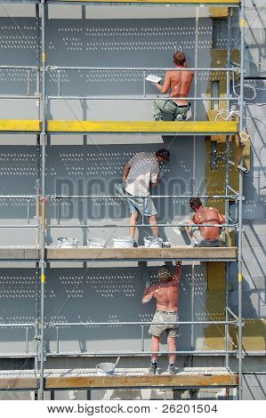 Four plasterers working outside on scaffolding