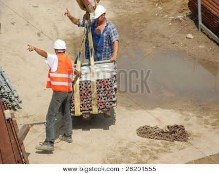 Two construction workers giving instruction to crane operator for positioning the load