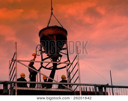 Silhouettes of construction workers pouring concrete mix at the building site