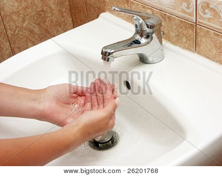 Woman washing hands with soap in bathroom
