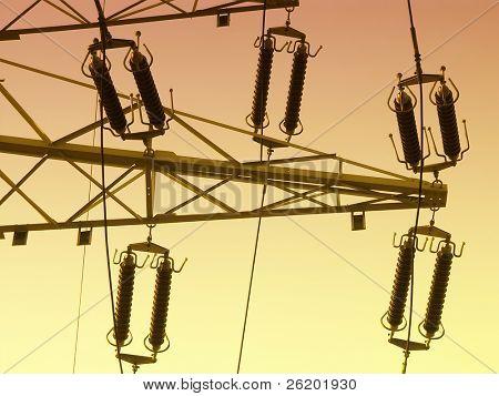 High voltage pylon with insulators over sunset sky