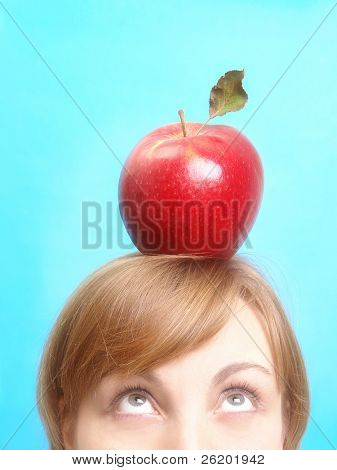 Woman looking up with red sweet apple resting on top of her head