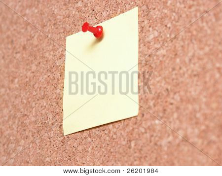 Yellow blank post-it note affixed to the corkboard with red pin