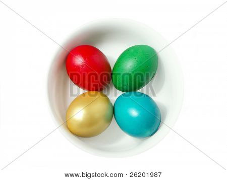 Four easter eggs painted in golden, red, green and blue color in white bowl over white