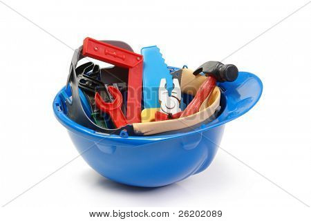 Set of plastic toy tools in blue helmet over white background