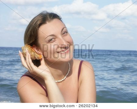 Young woman at the beach putting seashell up to her ear and listening its murmur