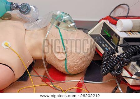 Maniquí de primeros auxilios con máscara respiratoria y sensores conectados a la unidad de Electrocardiógrafo