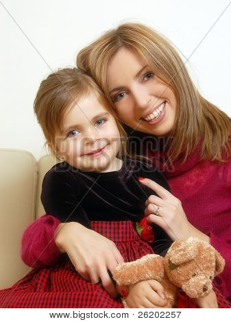 Young mom and her cute little daughter holding teddy-bear posing happily sitting on sofa