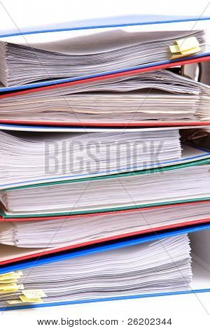 Pile of colorful ring binders over white background