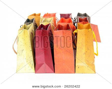 Two rows of colorful paper shopping bags over white