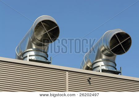 Two roof air condition outlets over blue sky