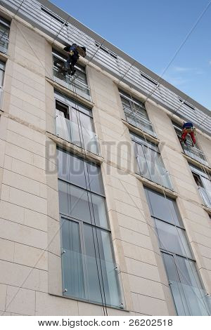 Two window washers washing office building windows hanging outside the building on ropes
