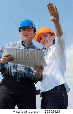 junges Paar tragen Helme holding Gebäude Projektdokumentation Visualisierung ihrer neuen zukünftigen hou