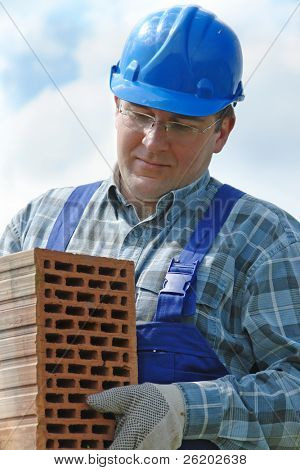 Construction worker in blue jumpsuit and helmet carrying hollow brick