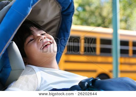 Disabled Five Year Old Boy In Wheelchair  By School Bus