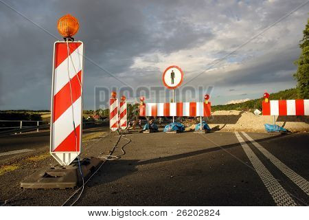 Road works marked with red and white striped road warning posts with orange beacons and barrier with no access sign