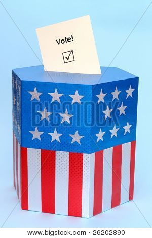 Yellow voting card half-inserted into ballot box decorated with american flag star and stripe colors over blue background