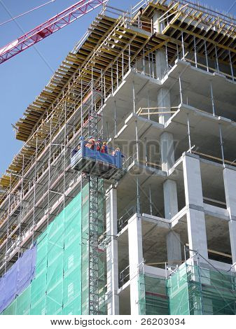 Group of construction workers going up the multistorey building using external lift to start their day shift