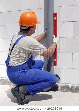 Fontanero usando el nivel para comprobar la plomada de tuberías de aguas residuales de pvc montada dentro de casa sin terminar