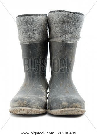 Dirty rubber-soled felt insulated boots shot over white
