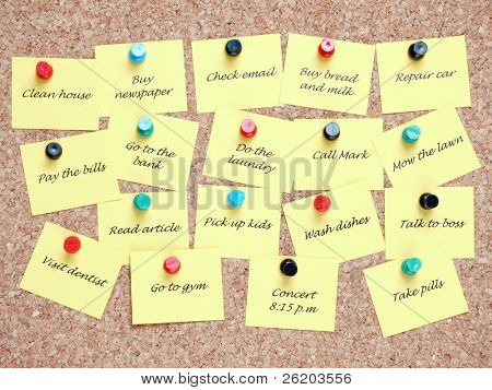 Yellow post it notes with various written to-do tasks affixed to the corkboard