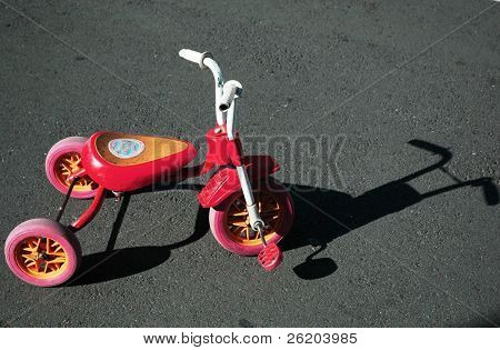 Child tricycle with harsh shadow