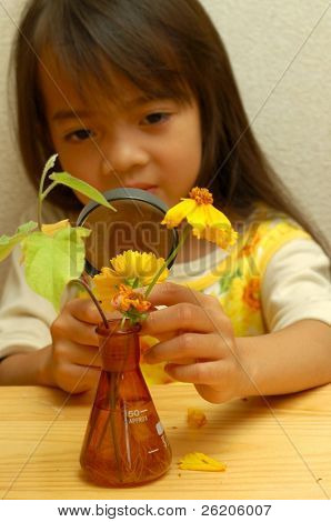 Little girl observing a flower through  magnifying glass