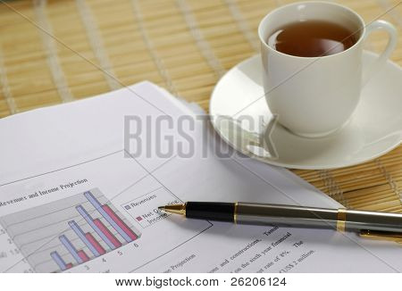Financial report, a pen and a cup of tea