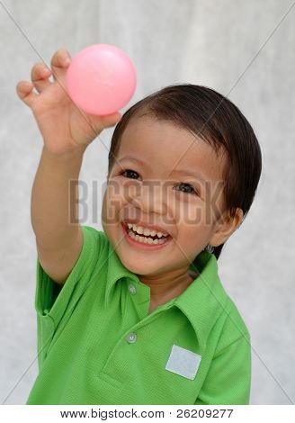 Little boy playing with little pink ball