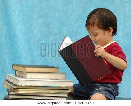 Two years old boy reading book