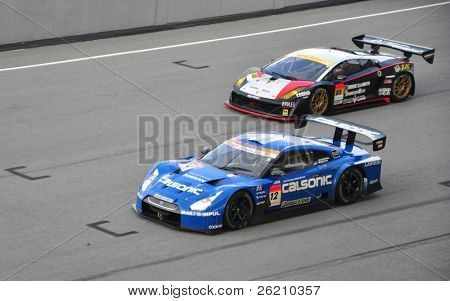 SEPANG, MALAYSIA - JUNE 20 : Super GT drivers in battle for position during the Super GT International Series, Round 4 on June 20, 2010 in Sepang International Circuit, Malaysia.