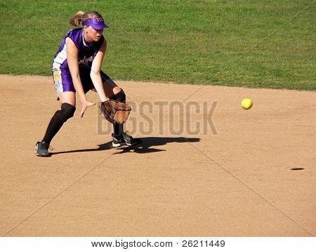 Girl Softball Player catching a bouncing Ball