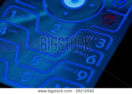 A closeup of a cell phones illuminated key pad and numbers