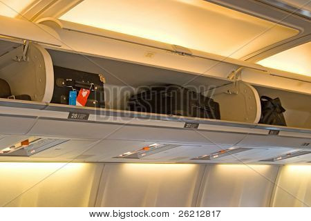 The interior of an airplane cabin with seats, passengers and baggage