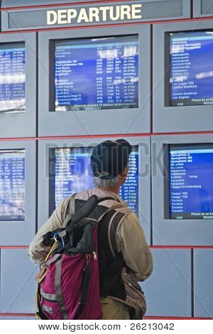 Travelers and businesspeople glance at the departure and arrival information at an airport for airline schedules