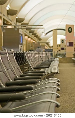An empty airport terminal waiting area with epmty seats for passengers and travelers going on vacation with baggage