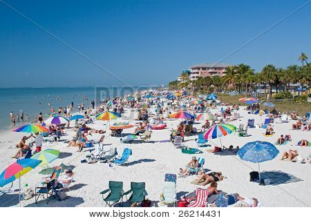 Tourists on the beach for summer vacation and in the water