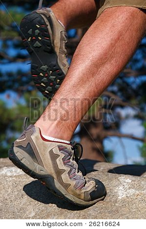 Trail runner climbing a steep rock in his path