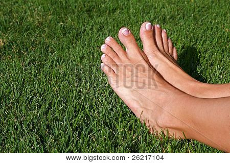 Relaxed feet of a woman laying in the grass