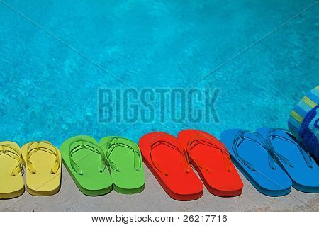 Colored flipflops of a family of four by the swimming pool