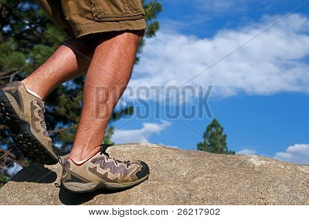 Trail runner climbing a steep rock in his path