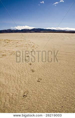 following footprints leading off towards the distant mountains and into the desert in Death Valley, California