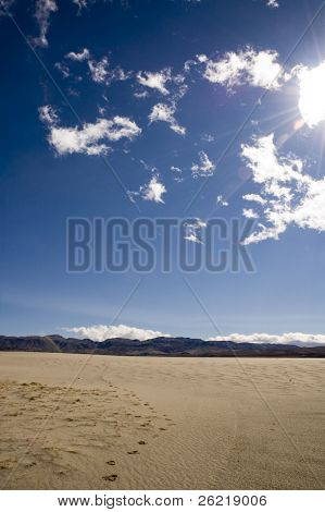 following footprints leading off towards the distant mountains and into the desert in Death Valley, under a scorching sun